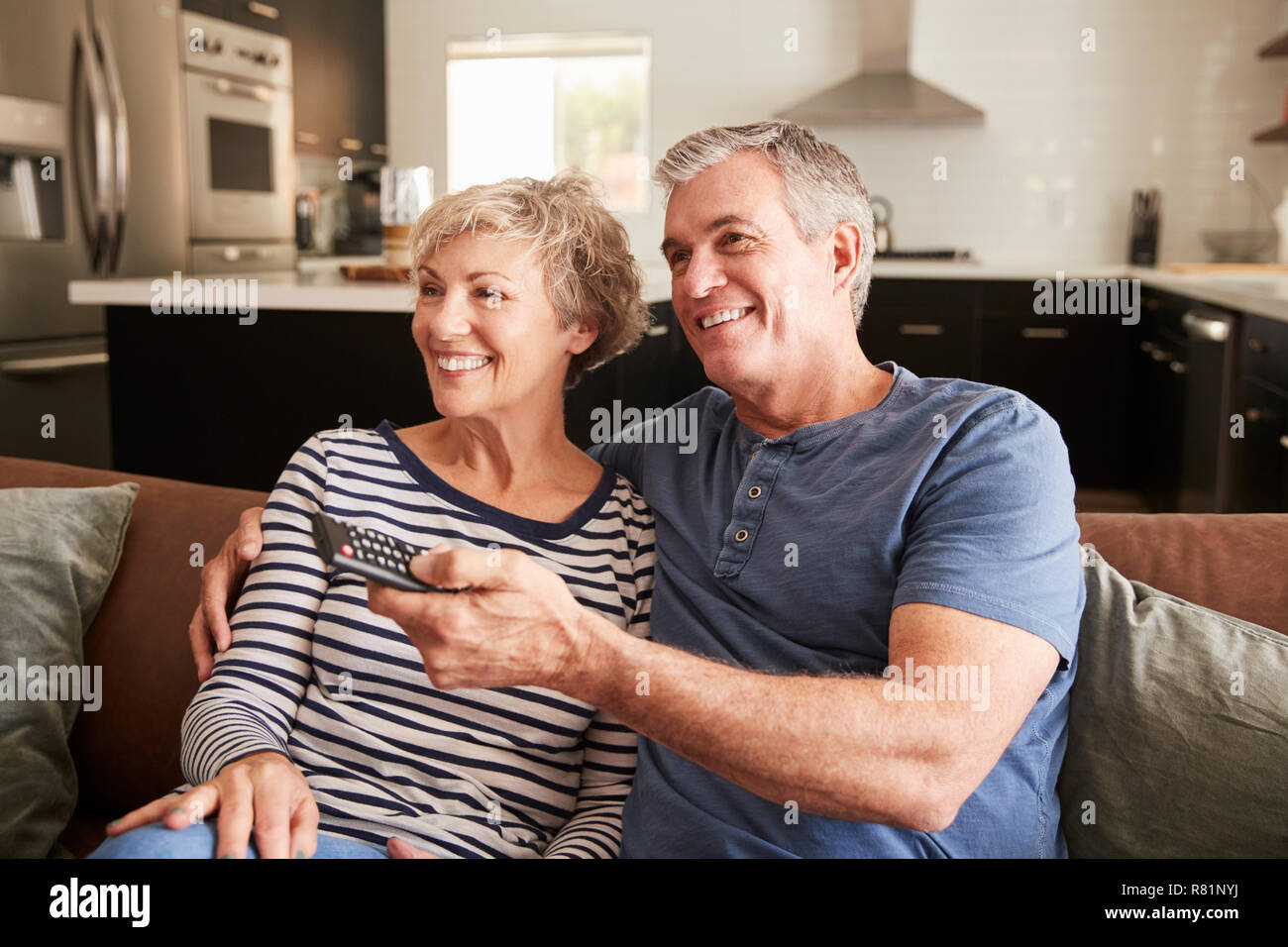 Senior couple sitting on couch watching television, close up Stock Photo