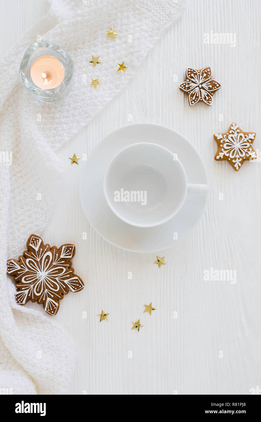Christmas background. Empty white cup, gingerbread, candles and knitted scarf on a white wooden background. Light still life. Flat lay, top view, copy Stock Photo