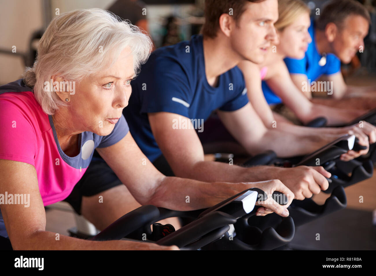 Close Up Of Group Taking Spin Class In Gym Stock Photo