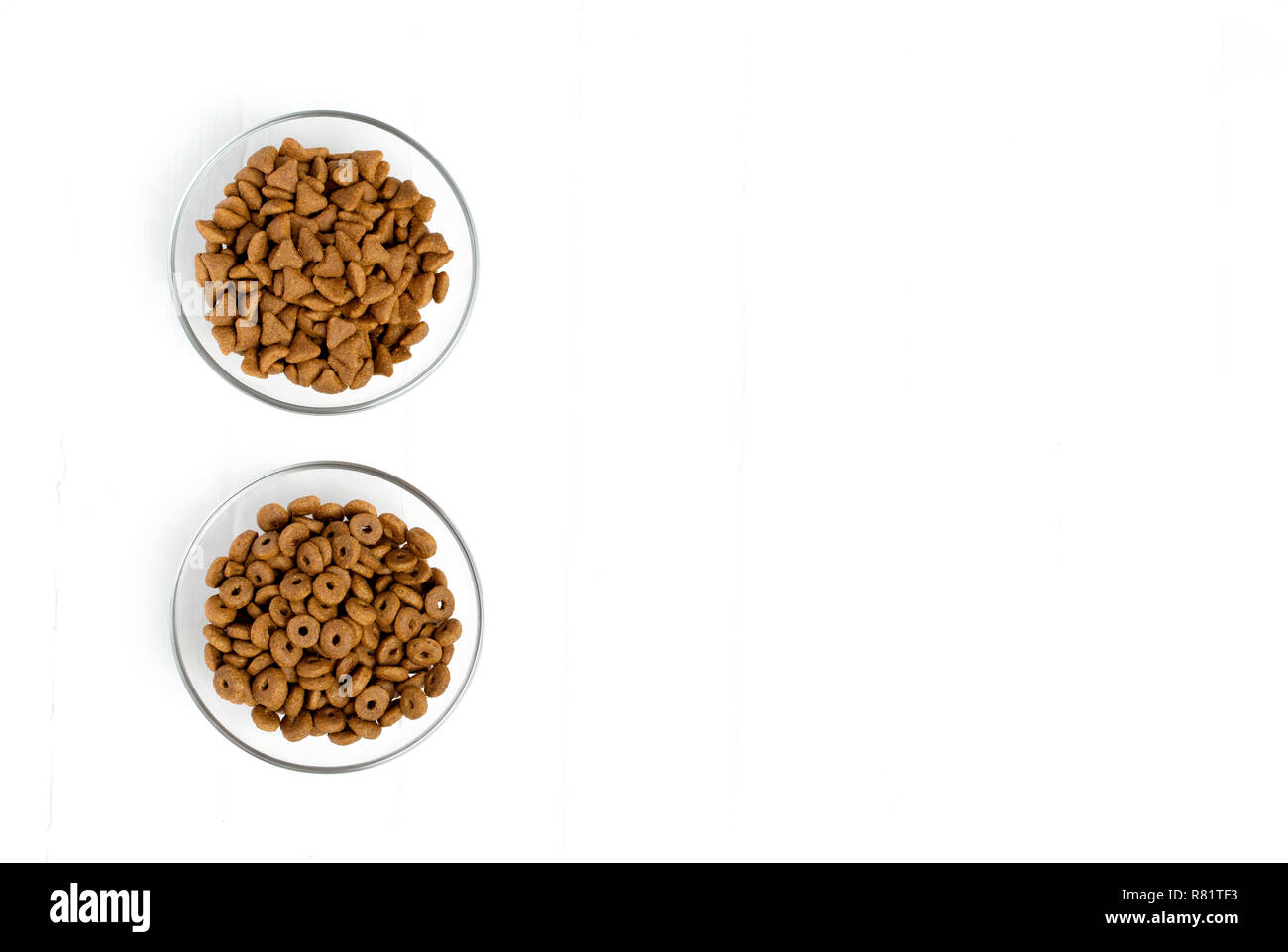 Dry cat food poured into a glass bowl on a white background - Stock Image