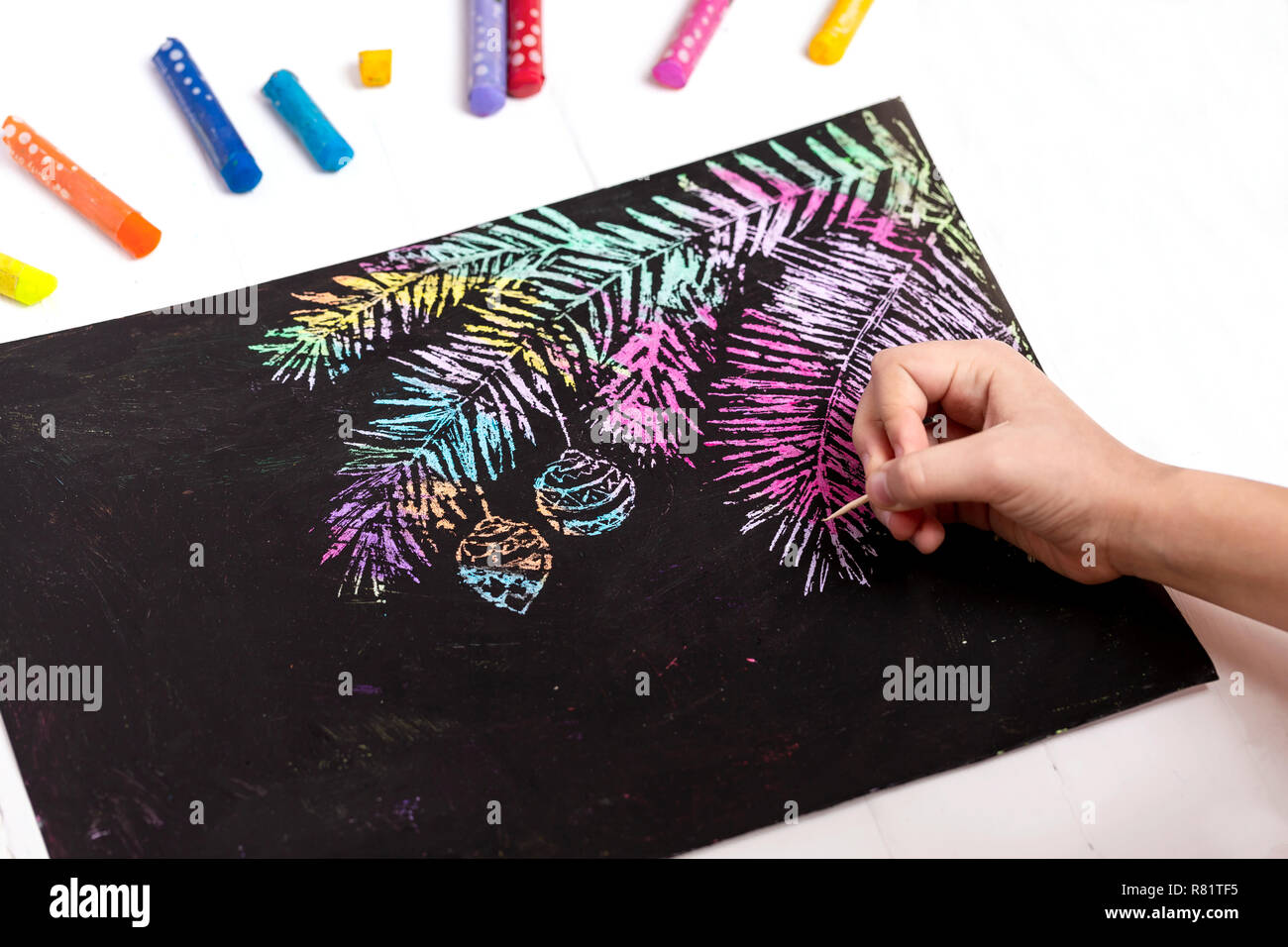 The child draws a pine branch with Christmas toys on a black background. - Stock Image