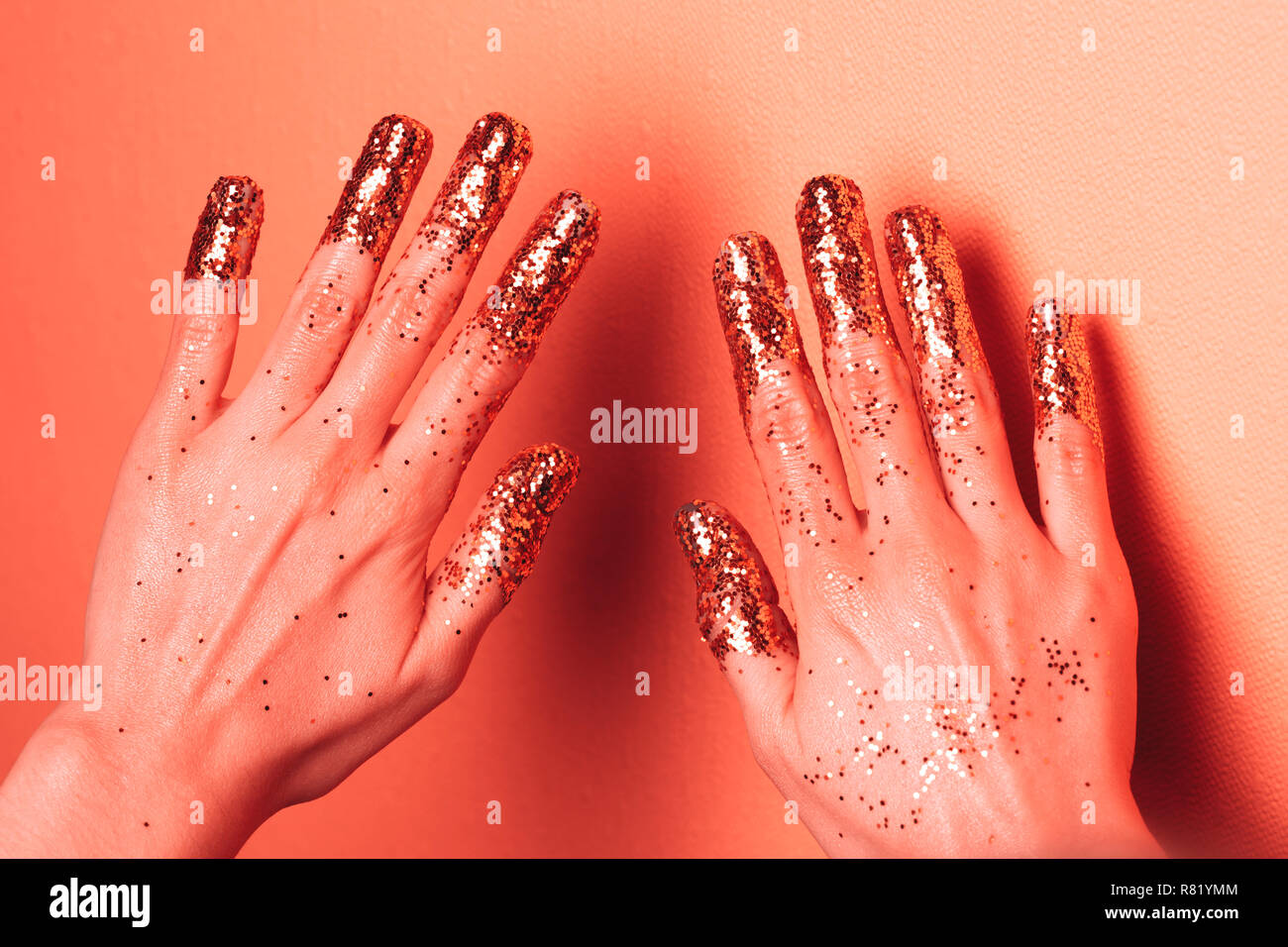 Manicure with glittering fingers. Art fashion inspired by Living Coral - colot of the Year 2019. Stock Photo