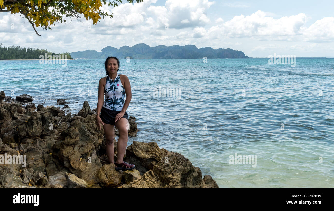 Asian woman in bathing suit smiling and standing on rocks on beach - Stock Image