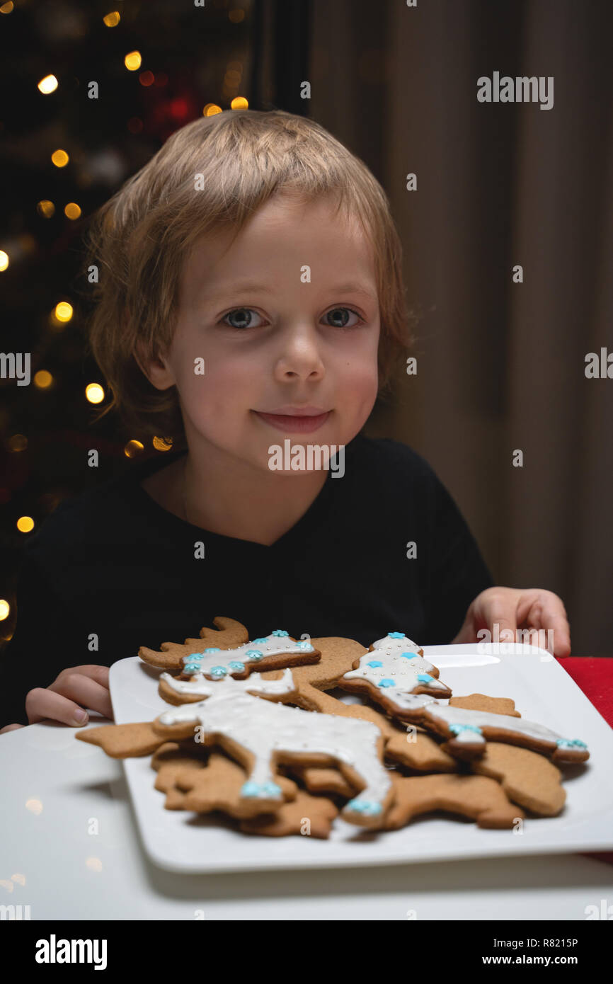 cute happy boy in hat holding delicious ginger cookie and smiling at camera - Stock Image