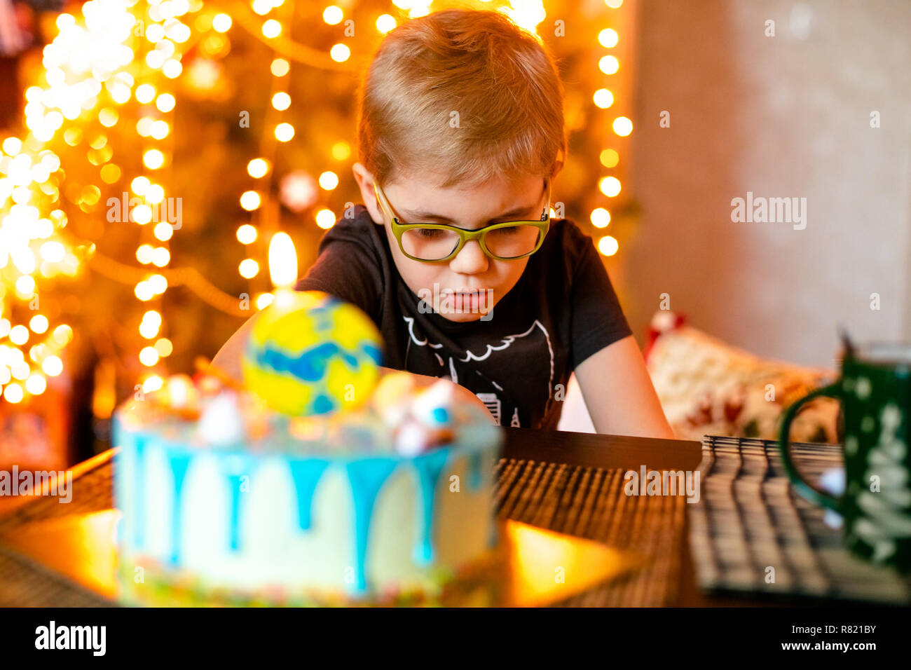 Beautiful Adorable Six Year Old Boy In Grey Shirt Celebrating His Birthday Blowing Candles On Homemade Baked Cake Indoor