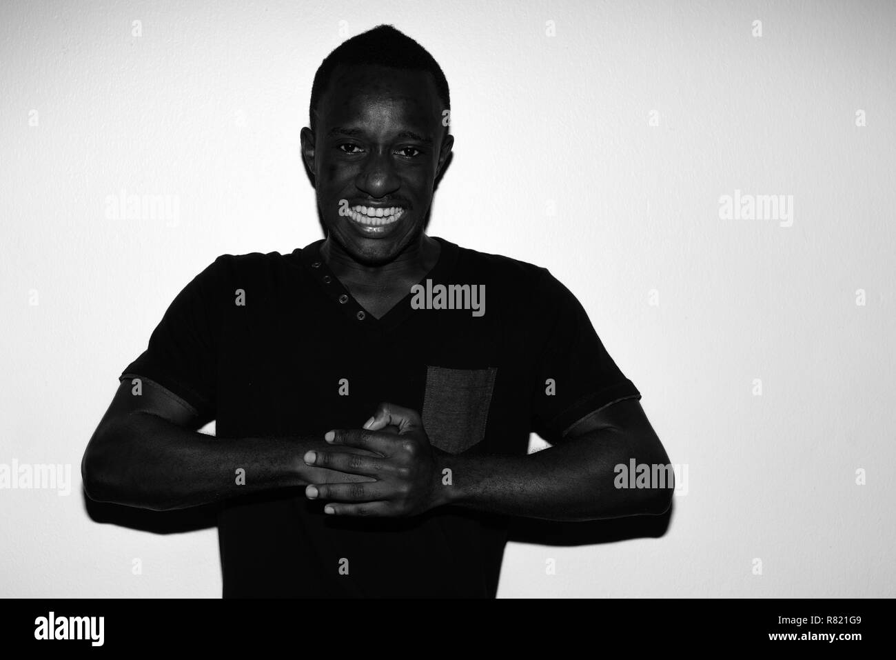 Spooky horror portrait of young angry African man in black and white - Stock Image