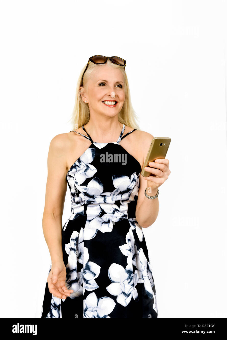 Attractive happy woman in pretty dress looking up after reading a text message, taken against white background - Stock Image