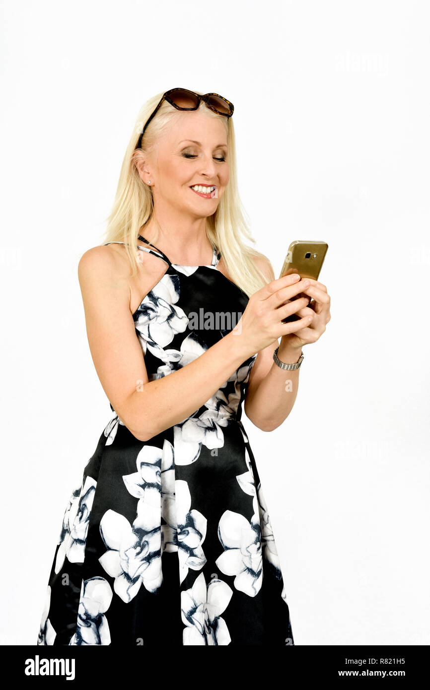 Attractive happy woman in pretty dress smiling whilst reading something on her mobile phone, taken against white background - Stock Image