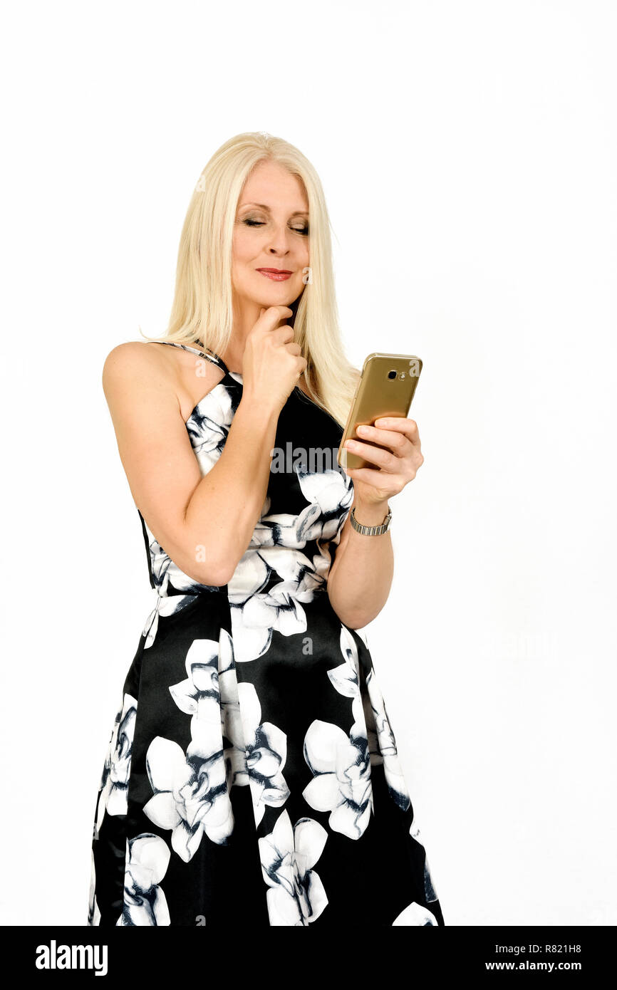 Attractive woman in pretty summer dress looking intrigued whilst using mobile phone, taken against white background - Stock Image