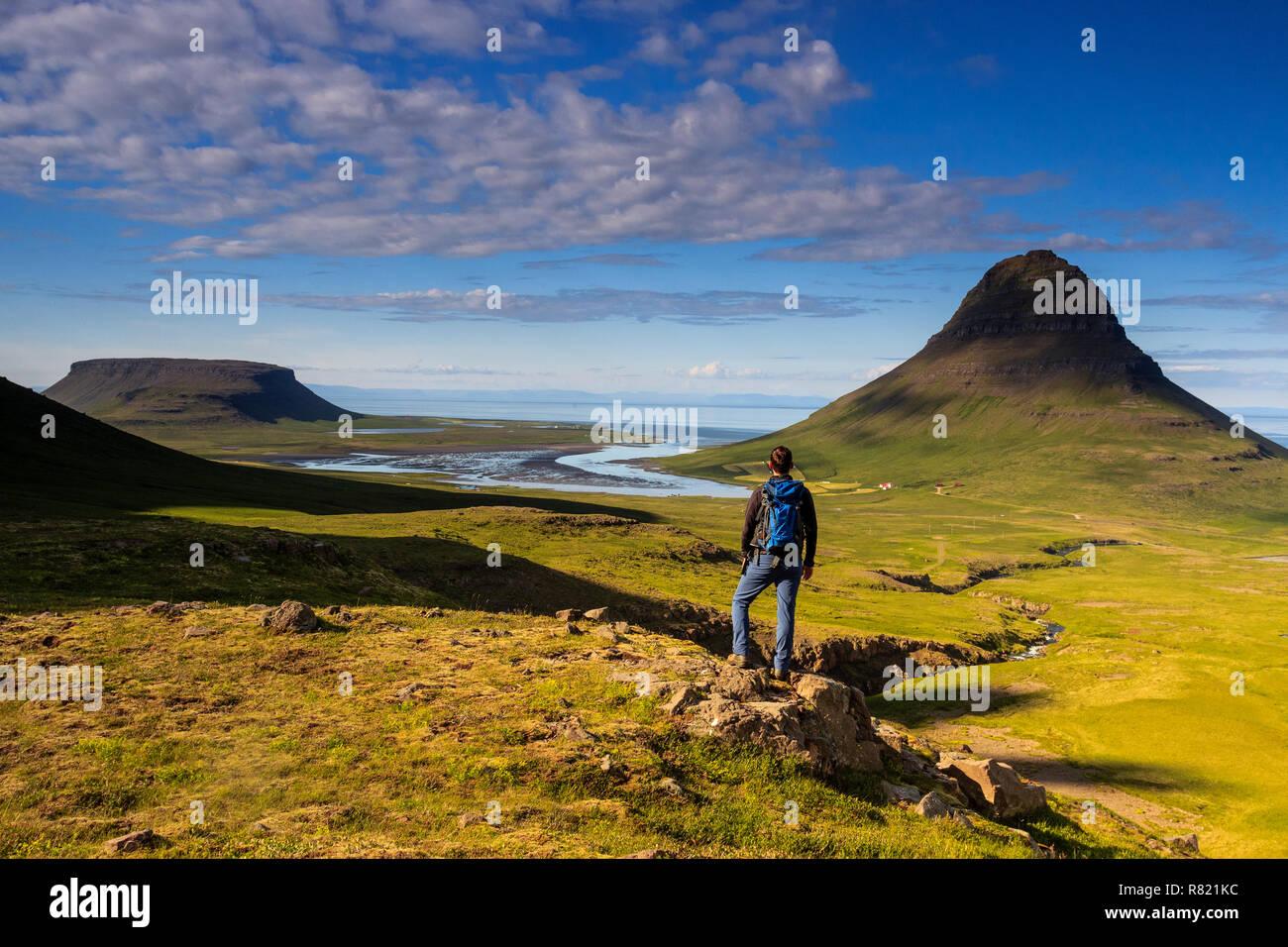 Hiker with magnificent view of kirkjufell and another table mountain in Iceland / Wanderer mit großartigem Ausblick auf Kirkjufell und einem Tafelberg - Stock Image
