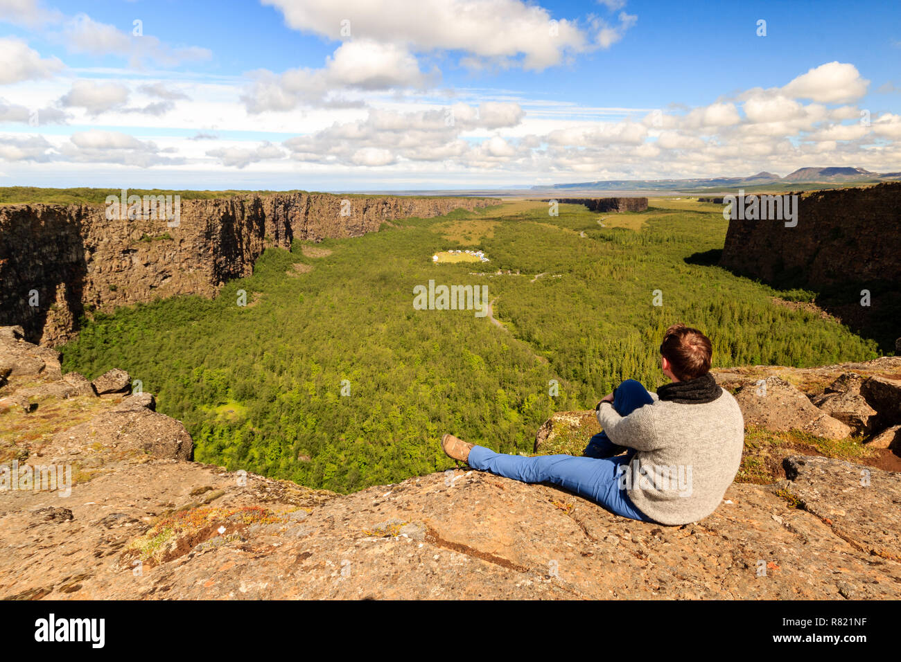 Hiker on the edge of Asbyrgi canyon in Iceland enjoying the view / Wanderer an der Kante der Asbyrgi Schlucht in Island Stock Photo