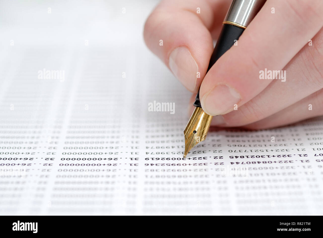Woman's hand holding pen, stock quotes in background Stock