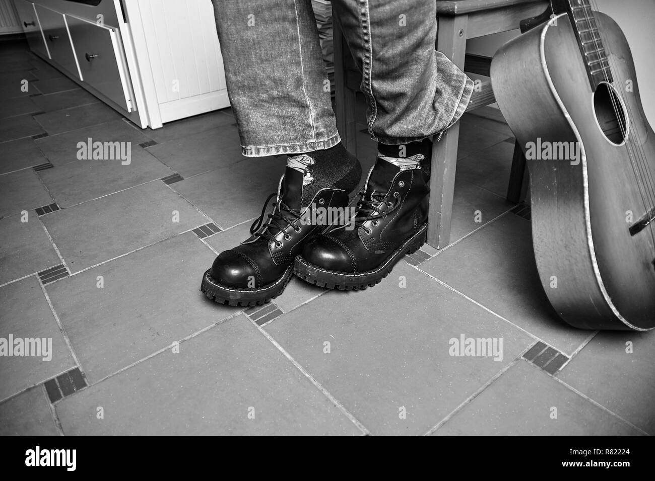 Rock and roll concept. Black boots and classic guitar. Black and white image - Stock Image