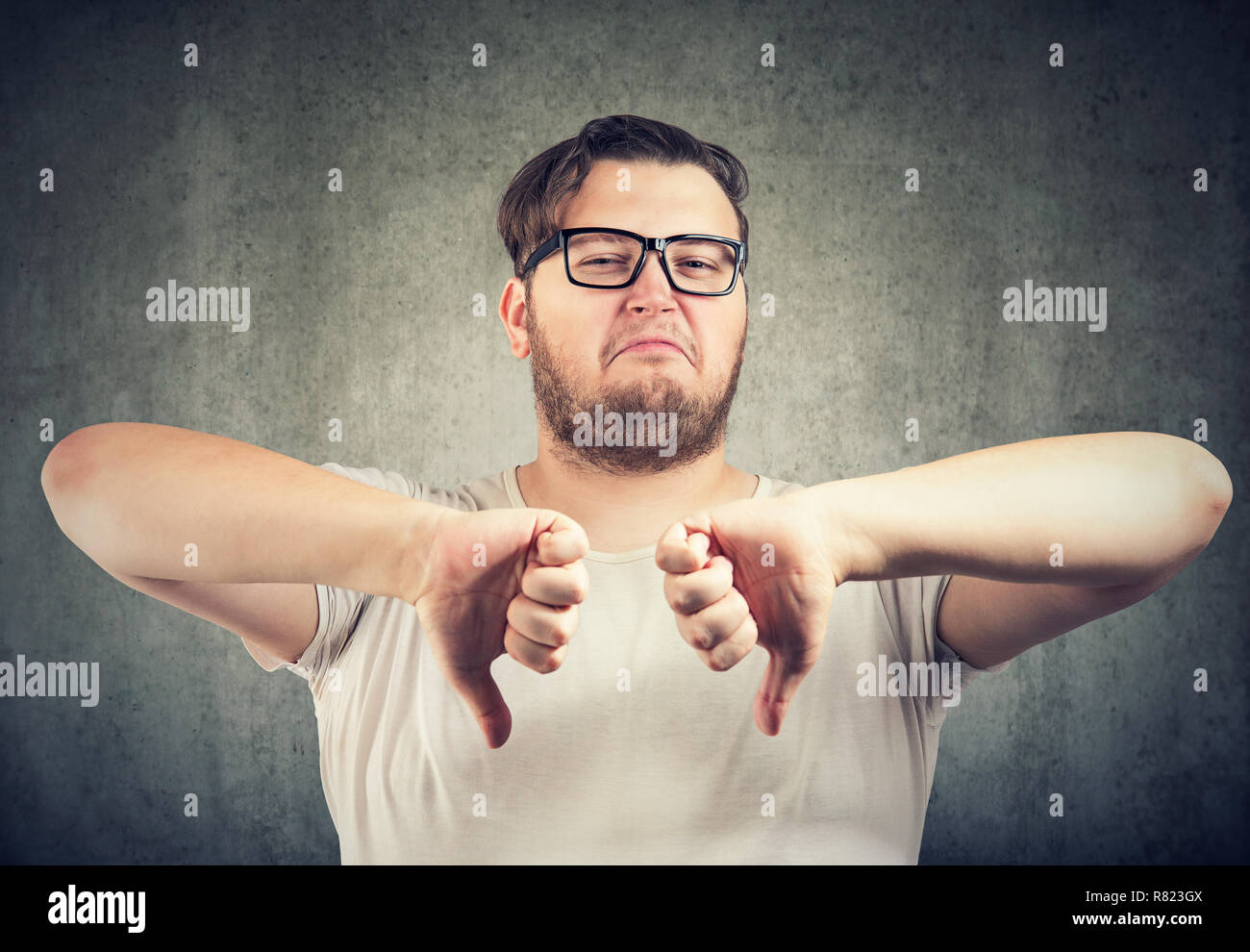 Young bearded man in glasses holding thumbs down showing dislike on gray background - Stock Image
