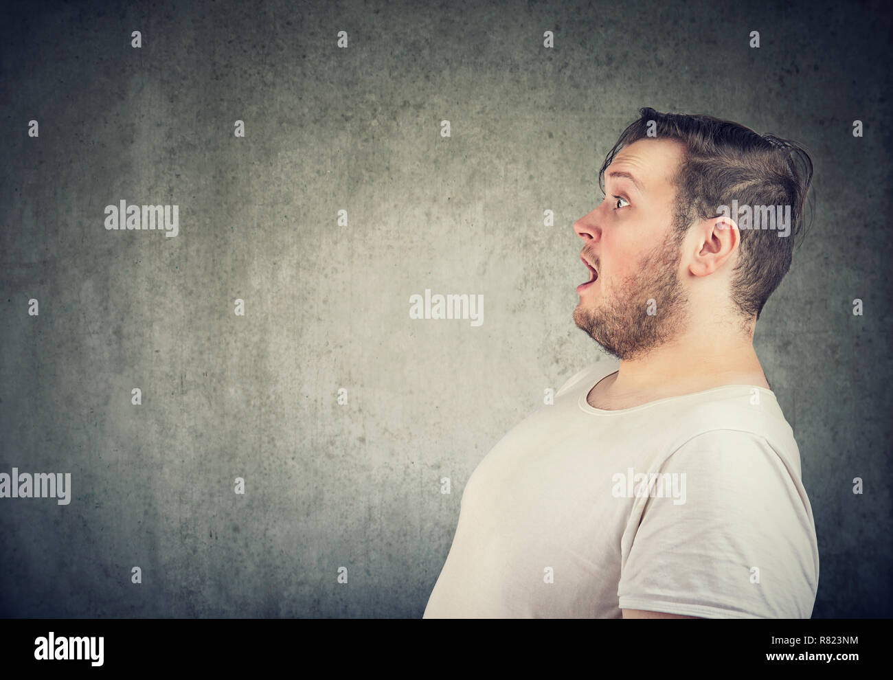 Side view of chubby man in white t-shirt looking away in amazement with mouth opened on gray background - Stock Image