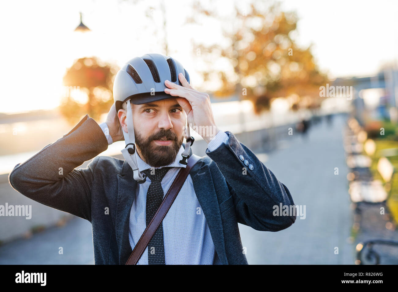 Businessman commuter traveling home from work in city, putting on a bicycle helmet. Stock Photo