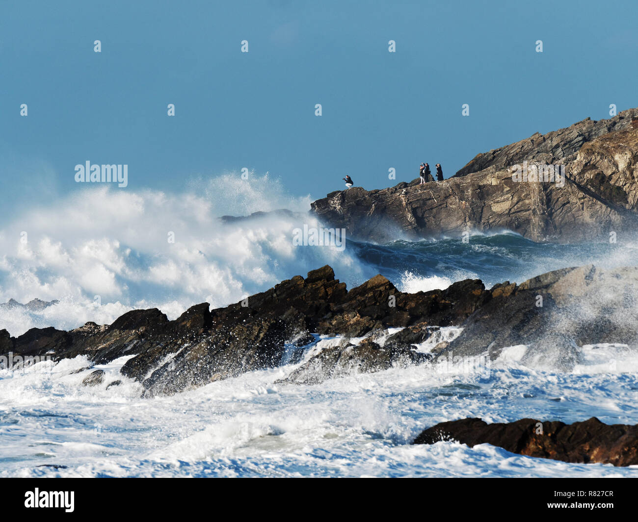 Danger family oblivious to dangerous wave conditions at the coast - Stock Image