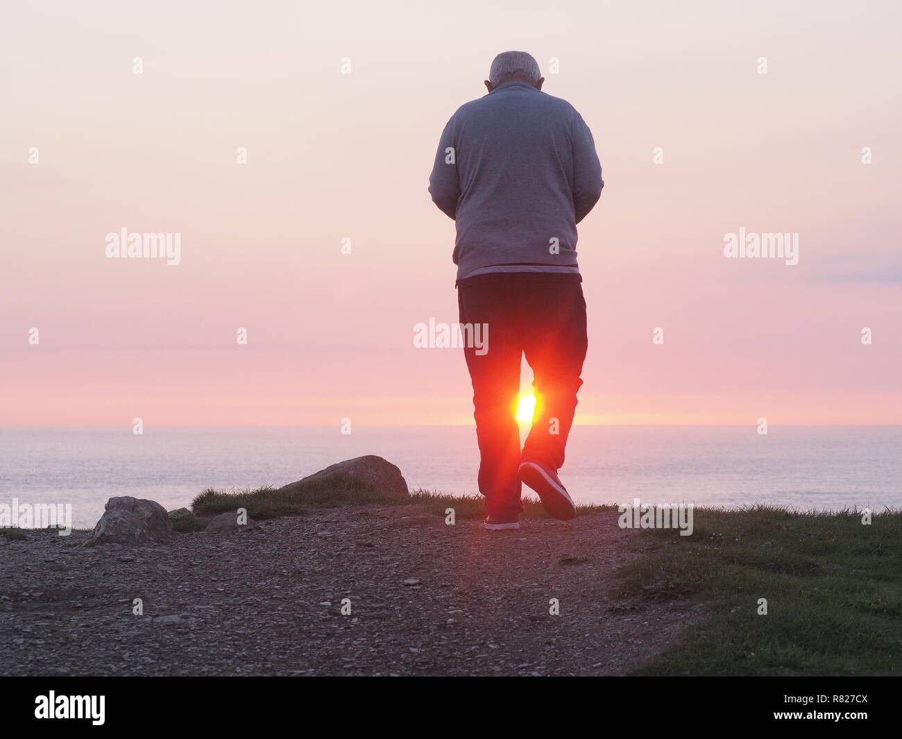 Older man framed by sunset rear view - Stock Image