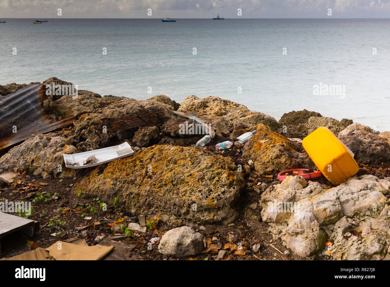 Discarded plastic and other waste litters a shoreline on the Caribbean island of Barbados - Stock Image