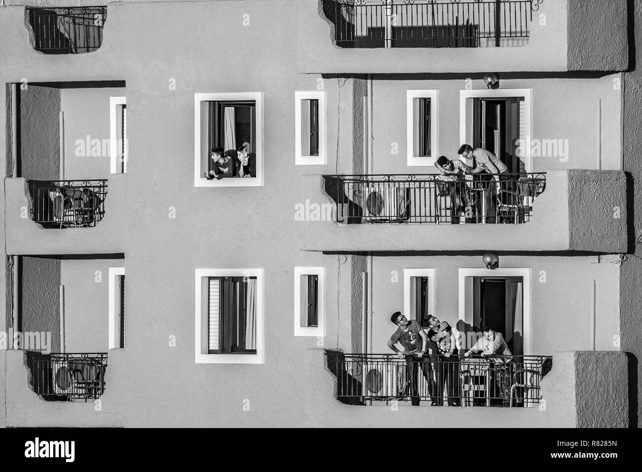 IGOUMENITSA, GREECE - MARCH 2, 2017: Group of young men speak to each other from the balconies and windows of a hotel on the boardwalk of the town as  - Stock Image