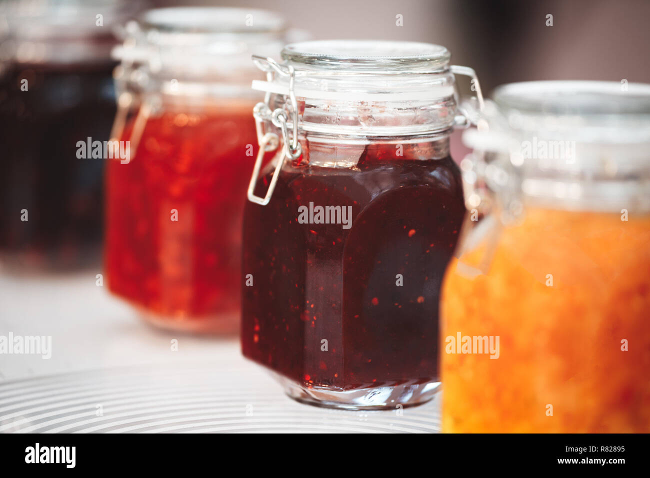 Close-up row of several glass with red yellow orange jars jam conserve confiture pozzy on table, breakfast concept, kitchen background, healthy eating - Stock Image