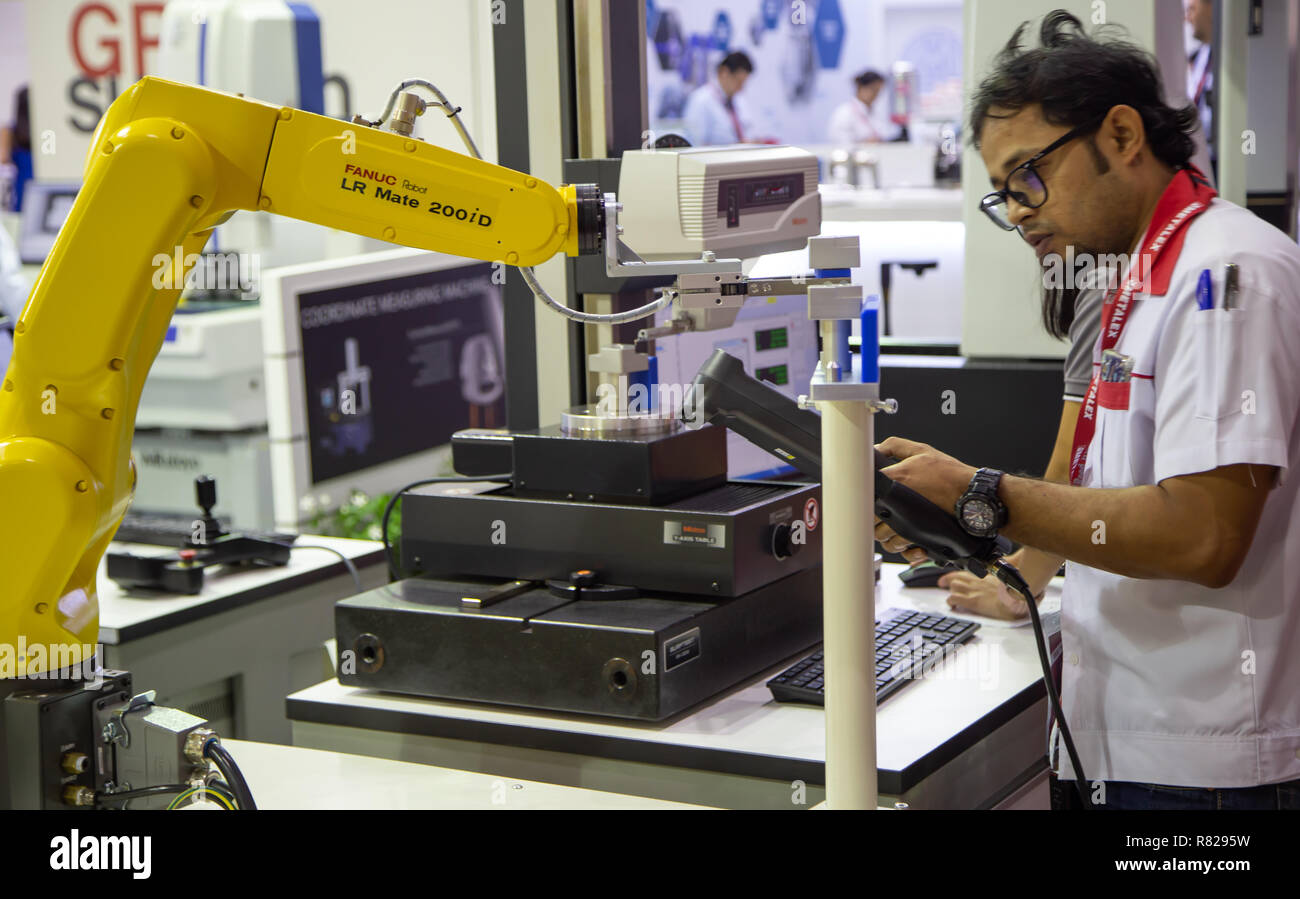 Bangkok, Thailand - November 21, 2018: Worker control robot arm to loading and unloading workpiece in Metalex 2018 - Stock Image