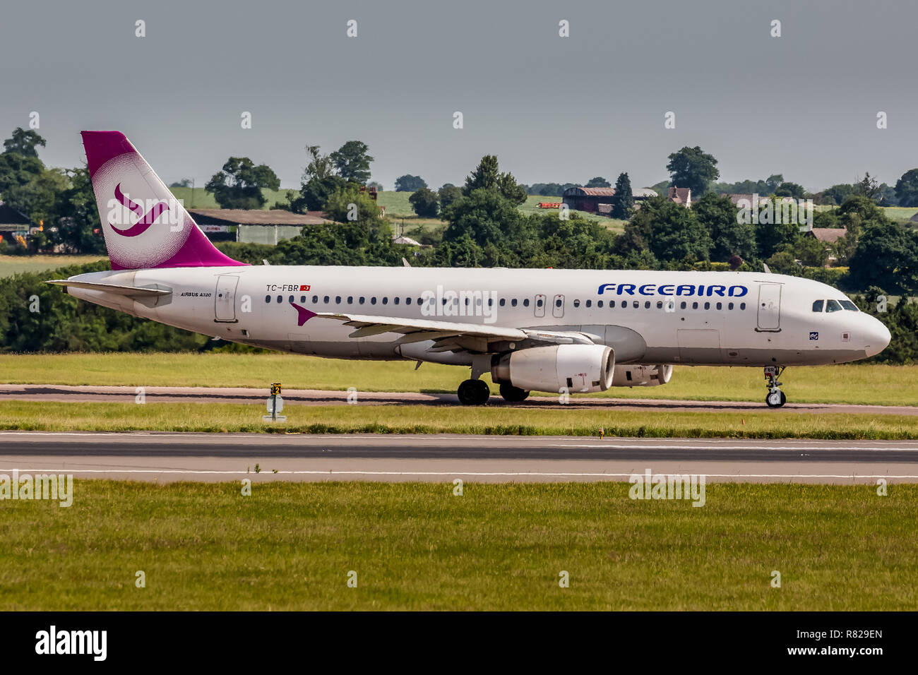 A Freebird Airlines Airbus A320, registration TC-FBR, taxying on the runway at London Luton Airport in England. - Stock Image