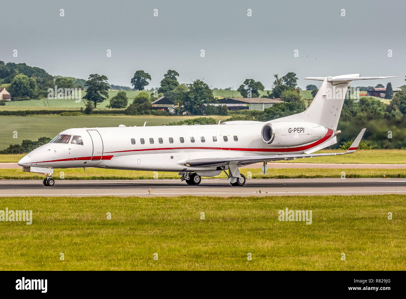An Embraer Legacy business executive jet plane, registration G-PEPI, taking off from London Luton Airport in England. - Stock Image
