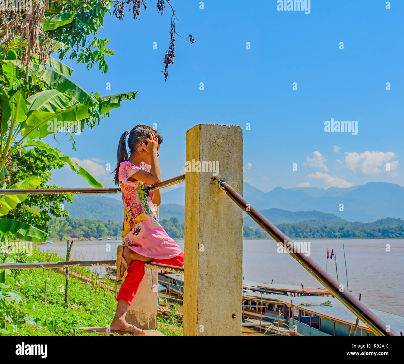 A small girl leaning on the railings by a village on the Mekong River looks out and thinks 'One day my boat will come' - Stock Image