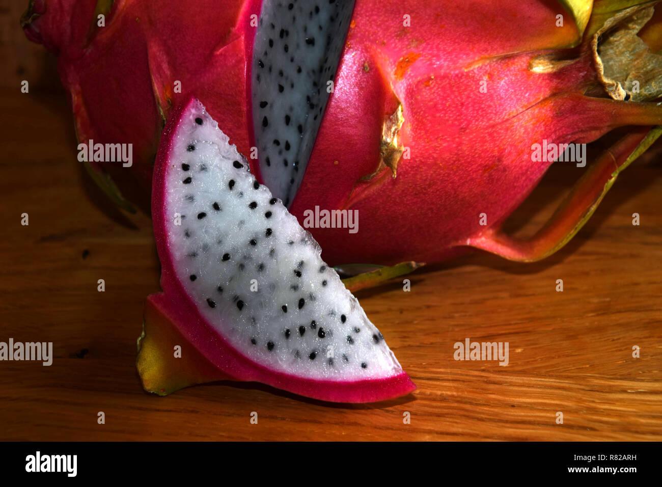 pitaya blanca or white-fleshed and pink-skinned ripe pitahaya fruit also called hylocereus undatus on wooden table, slices of ripe dragonfruit - Stock Image