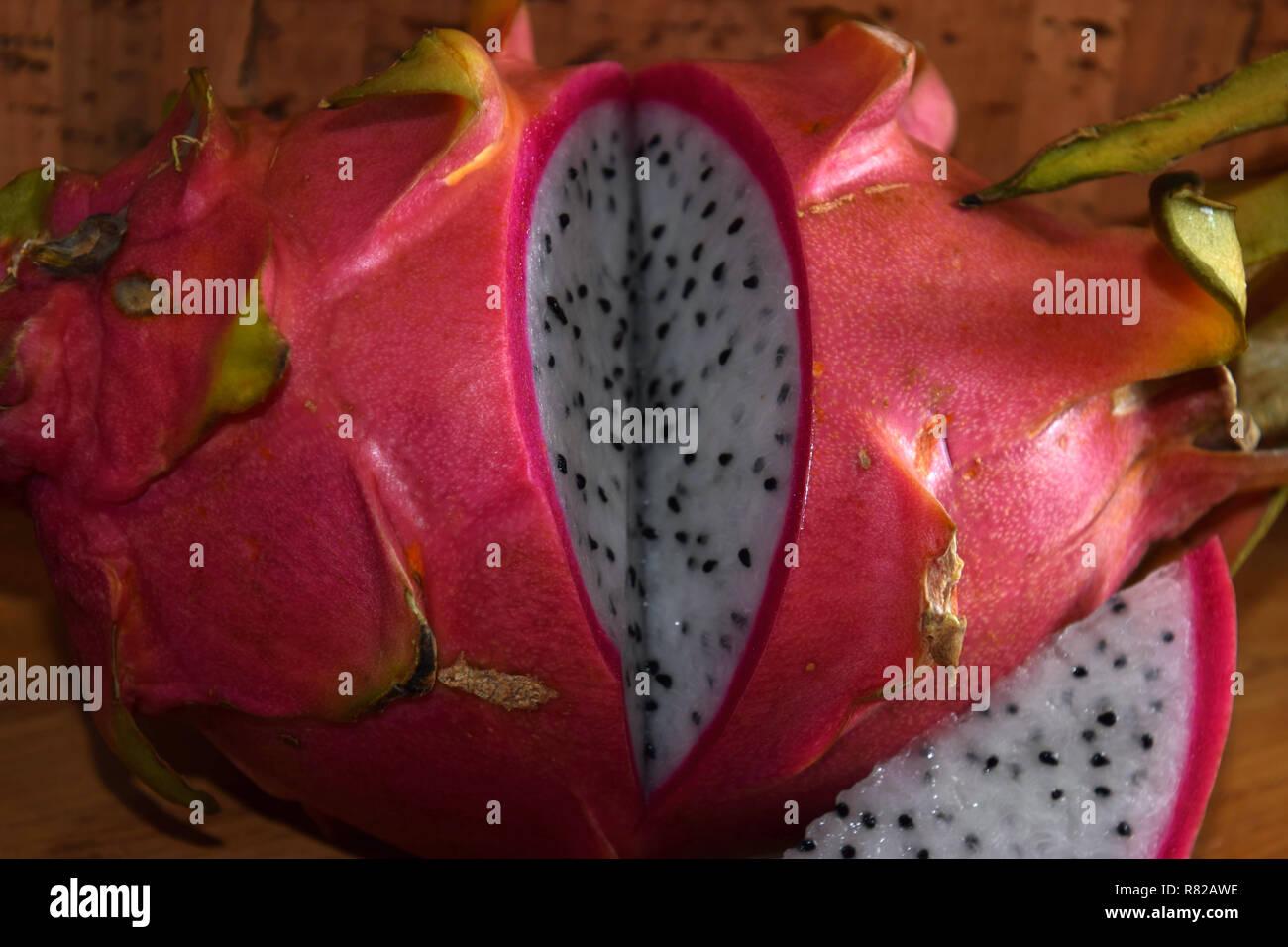 sliced dragon fruit, pitaya blanca or white-fleshed and pink-skinned ripe pitahaya fruit also called hylocereus undatus on wooden table - Stock Image