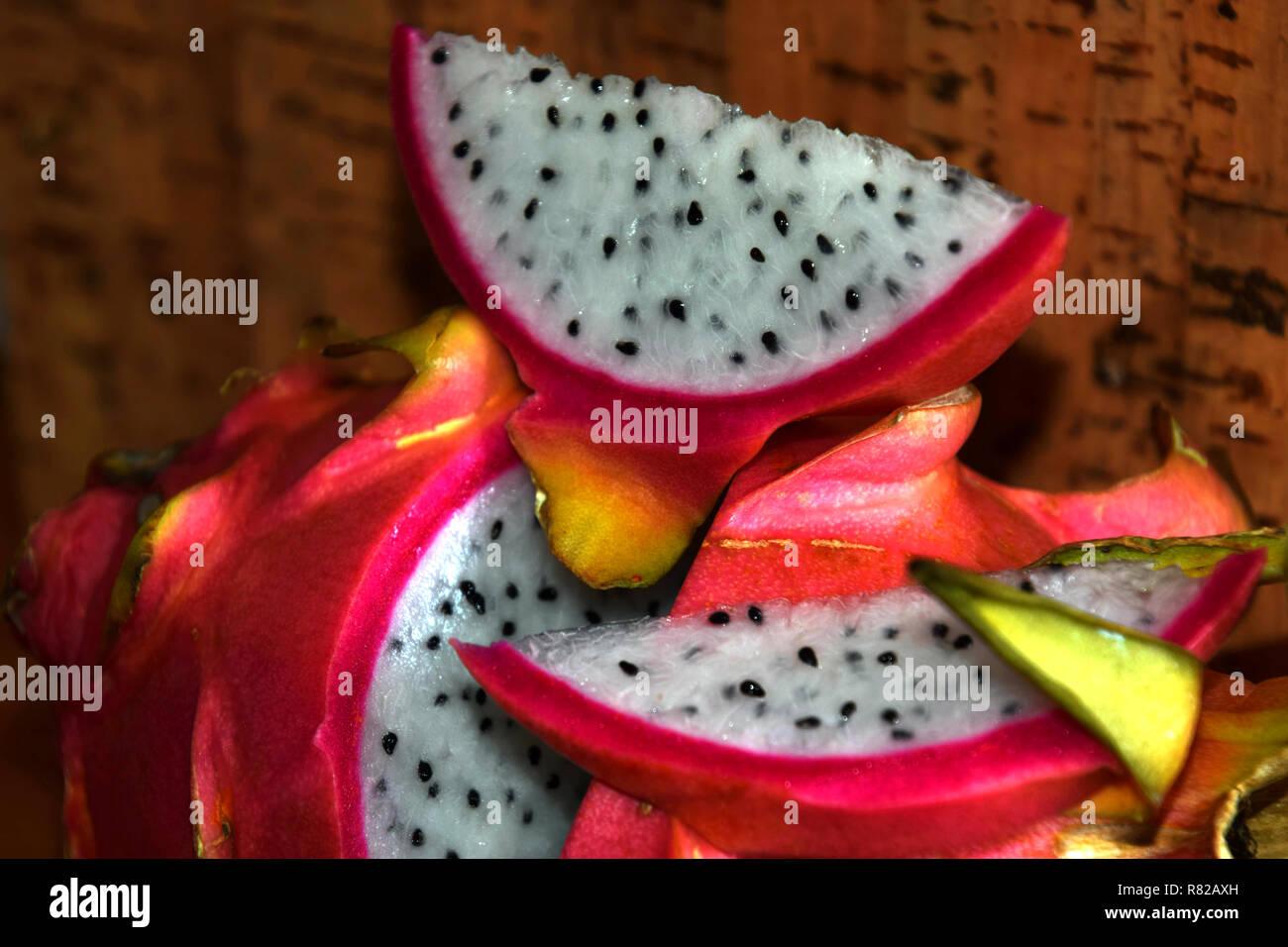 slice of dragon fruit in front of cork background , pitaya blanca or white-fleshed and pink-skinned ripe pitahaya fruit also called hylocereus undatus - Stock Image