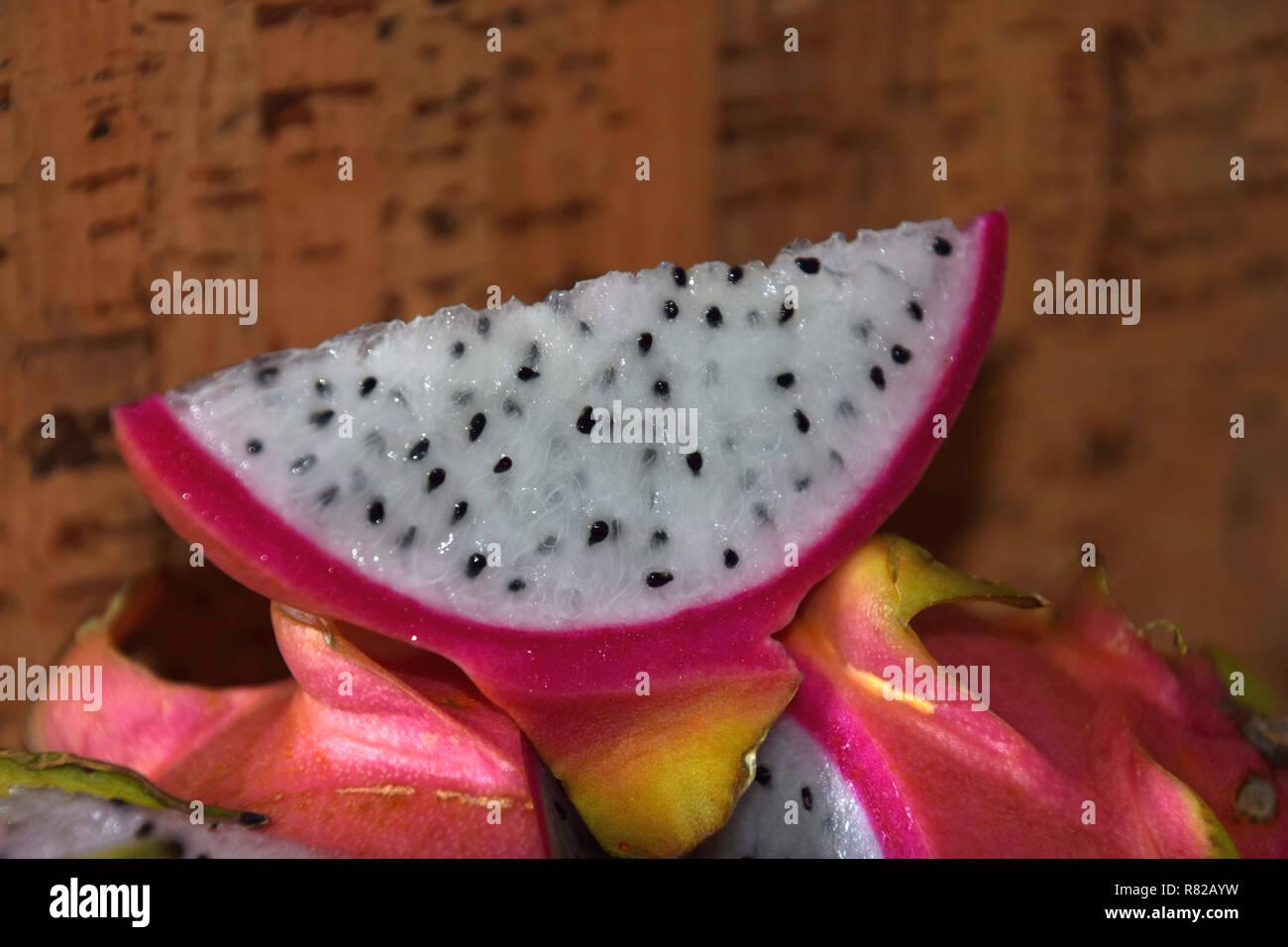 macro shot of slice of dragon fruit in front of cork background , pitaya blanca or white-fleshed and pink-skinned ripe pitahaya fruit also called hylo - Stock Image