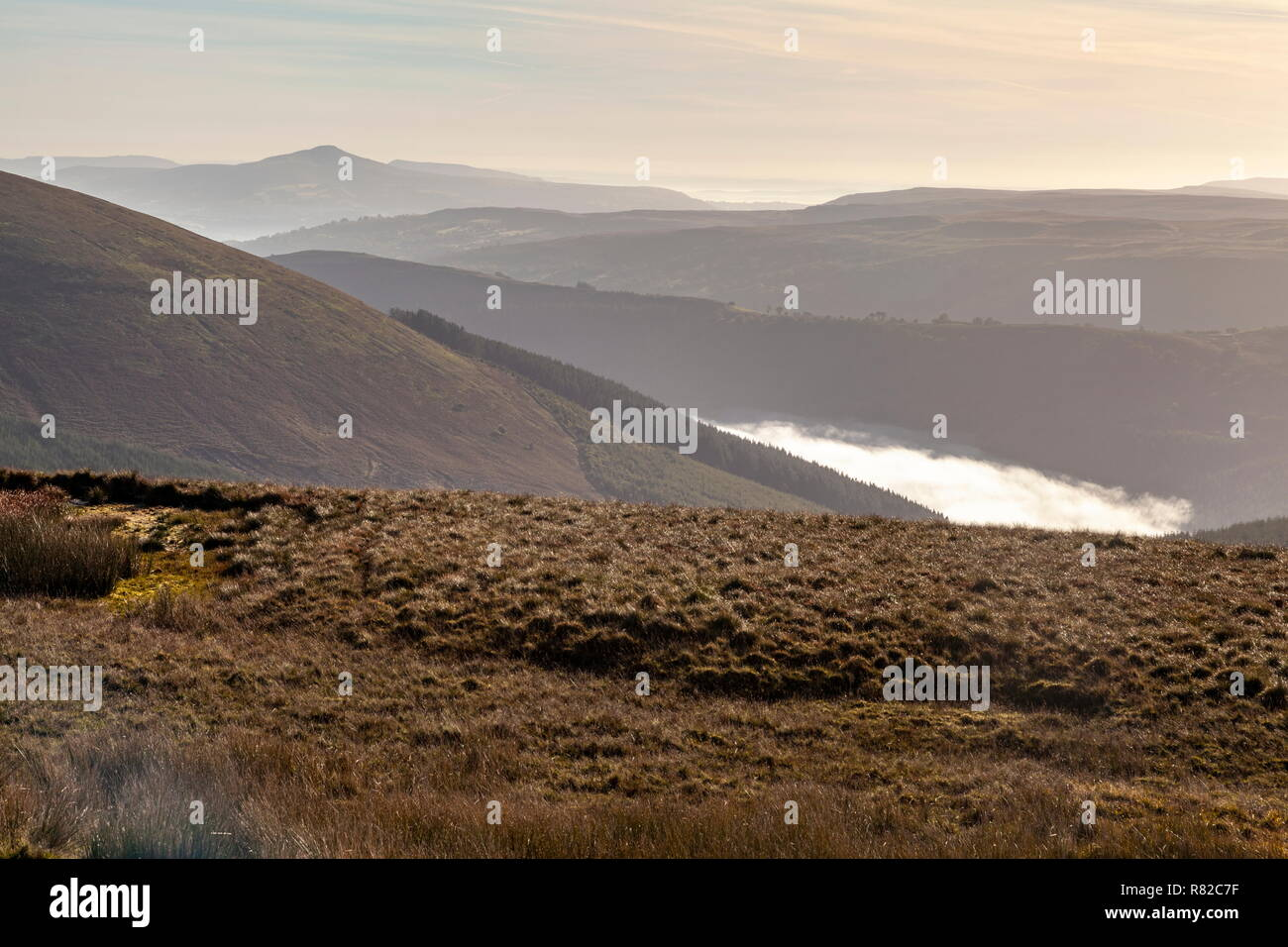 Early morning fog can be seen in the valley near Talybont reservoir, viewed from the summit of Torpantau, Brecon Beacons National Park - Stock Image