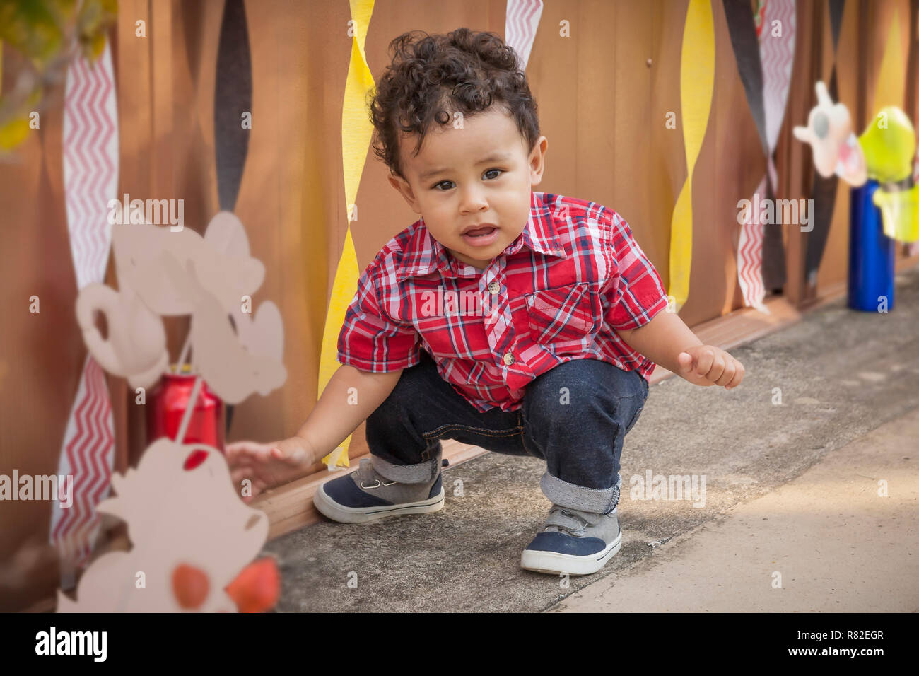 cac458719 Curly hair one-year-old wearing a red plaid shirt, blue jeans, and sneakers  look at the camera as he squats at his birthday party.