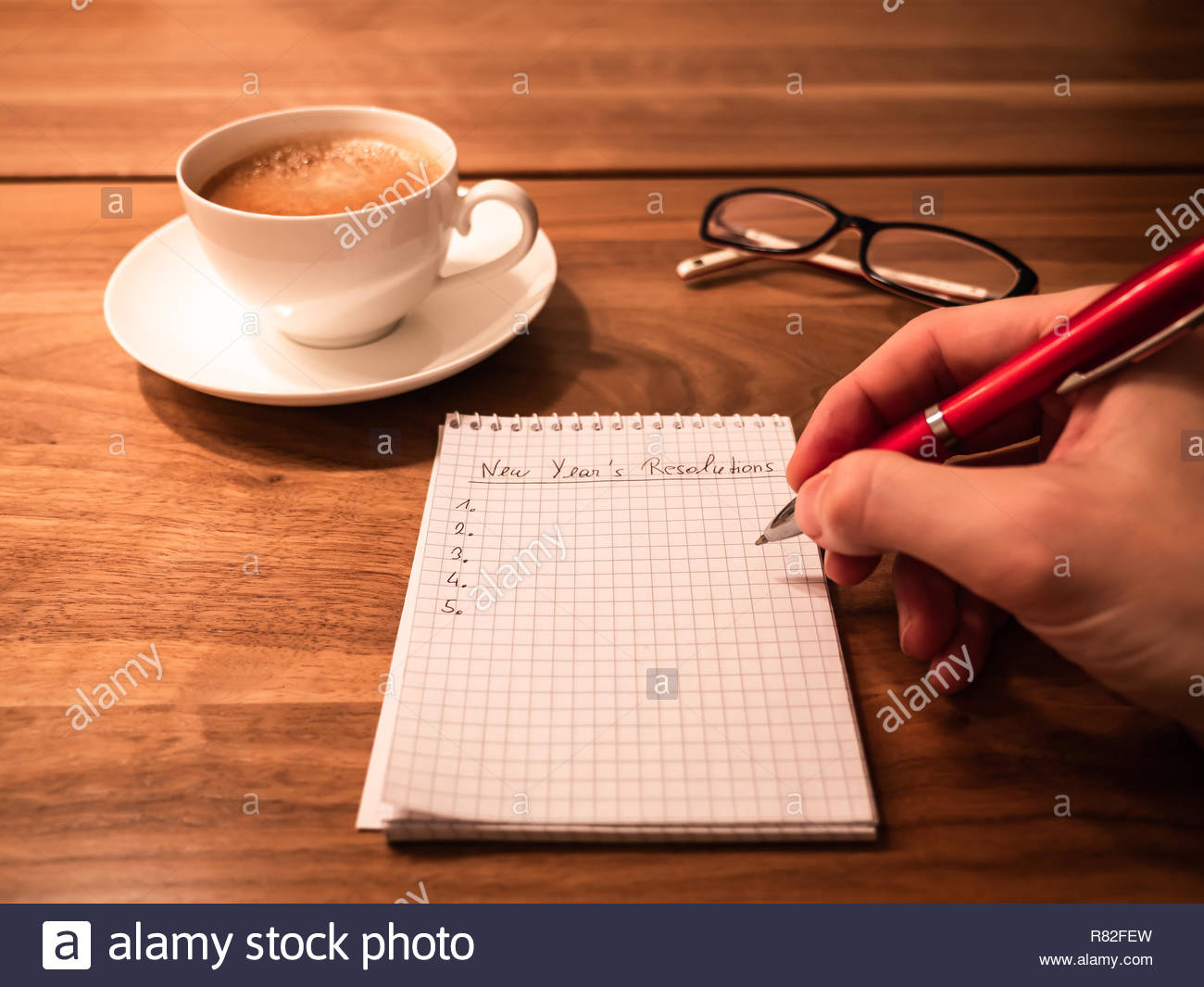 writing new years resolutions and goals with a pen on a notepad for the beginning of