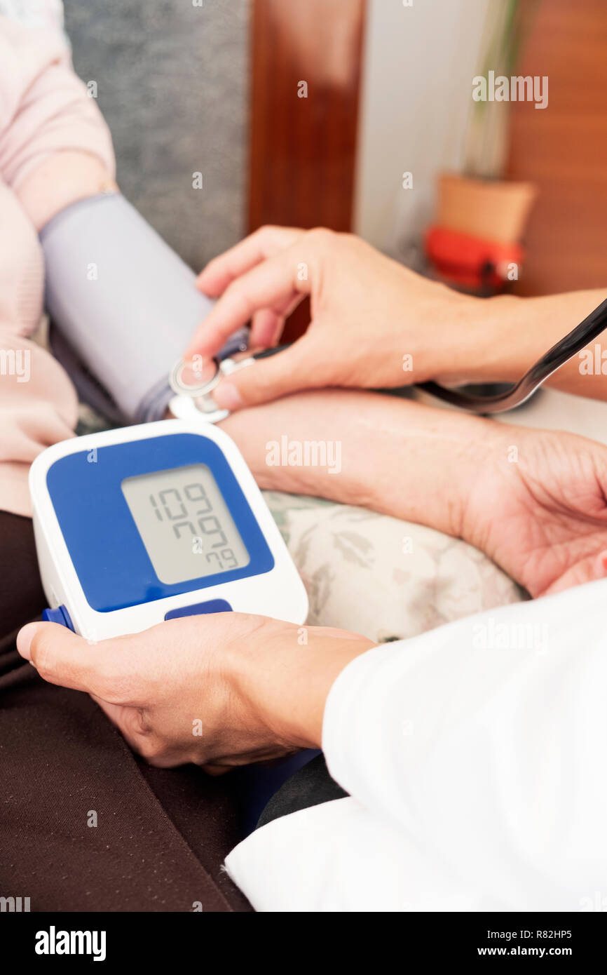 closeup of a caucasian doctor man, in a white coat, measuring the blood pressure of a senior caucasian patient woman with a sphygmomanometer, at her h - Stock Image