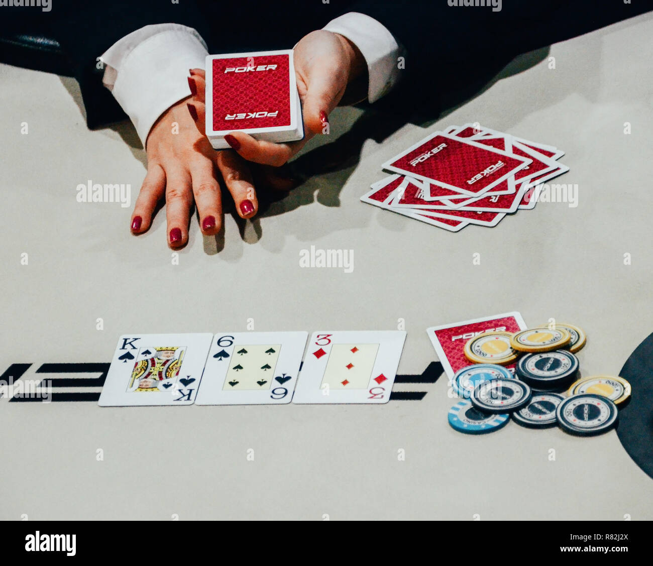 Close up of female dealer with deck of cards on her hand after dealing 3 cards on the table, with poker chips on the side - tournament texas hold 'em  - Stock Image