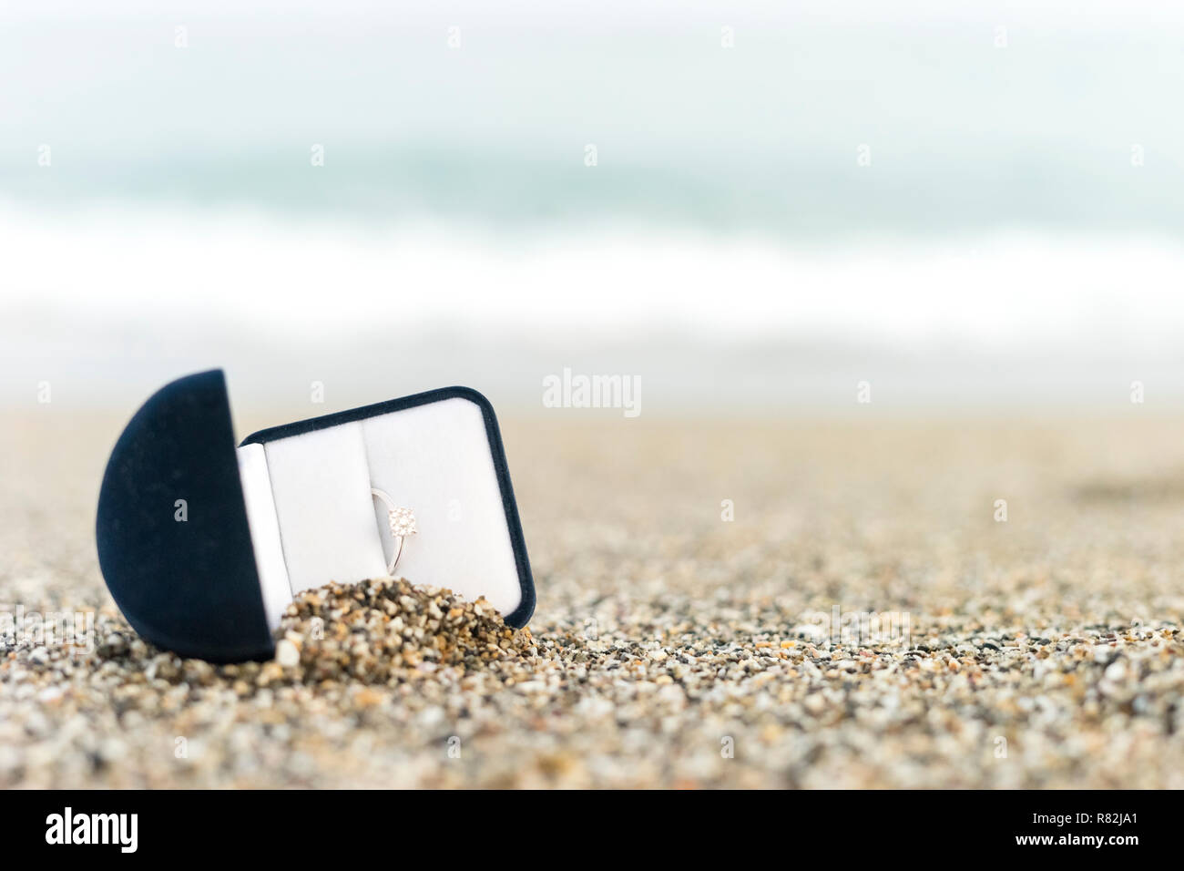 Engagement ring with diamond in elegant box on the beach - Stock Image