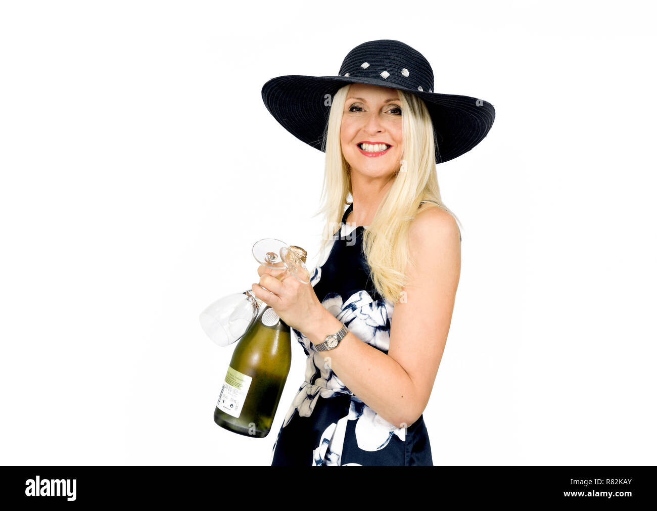 Attractive smiling woman in pretty dress holding a bottle of wine and two glasses, taken against white background - Stock Image