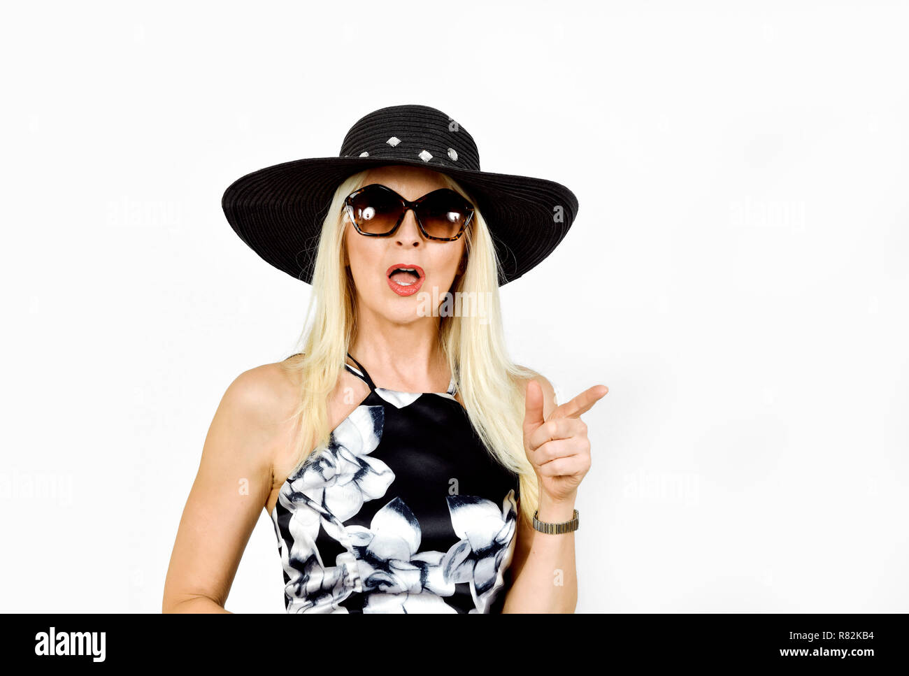 Attractive woman in pretty dress and hat with shocked expression and pointing finger, taken against white background - Stock Image