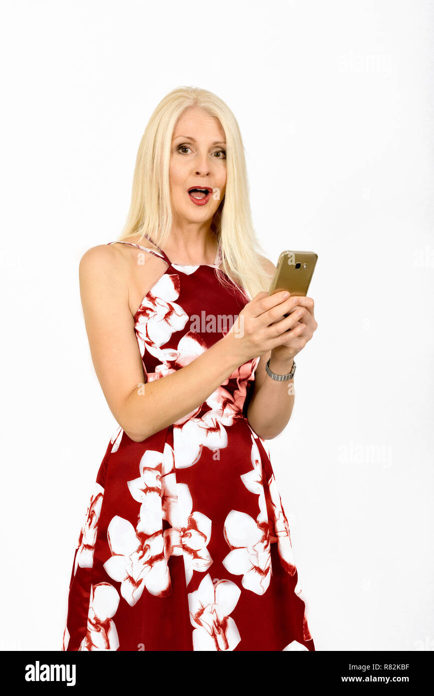 Attractive woman in pretty summery dress with a shocked expression whilst using her mobile phone, taken against white background - Stock Image