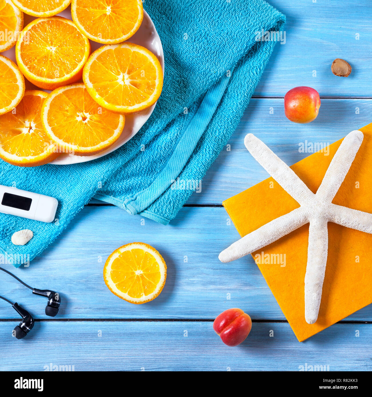 Oranges, towel, headphones and starfish on blue wooden background. Summer holiday concept - Stock Image