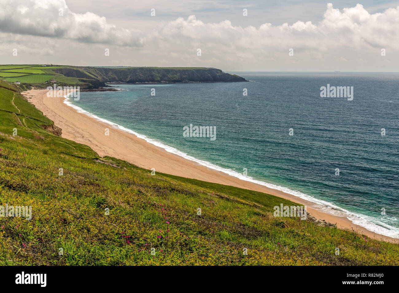 A long, deserted beach in Cornwall, England. - Stock Image