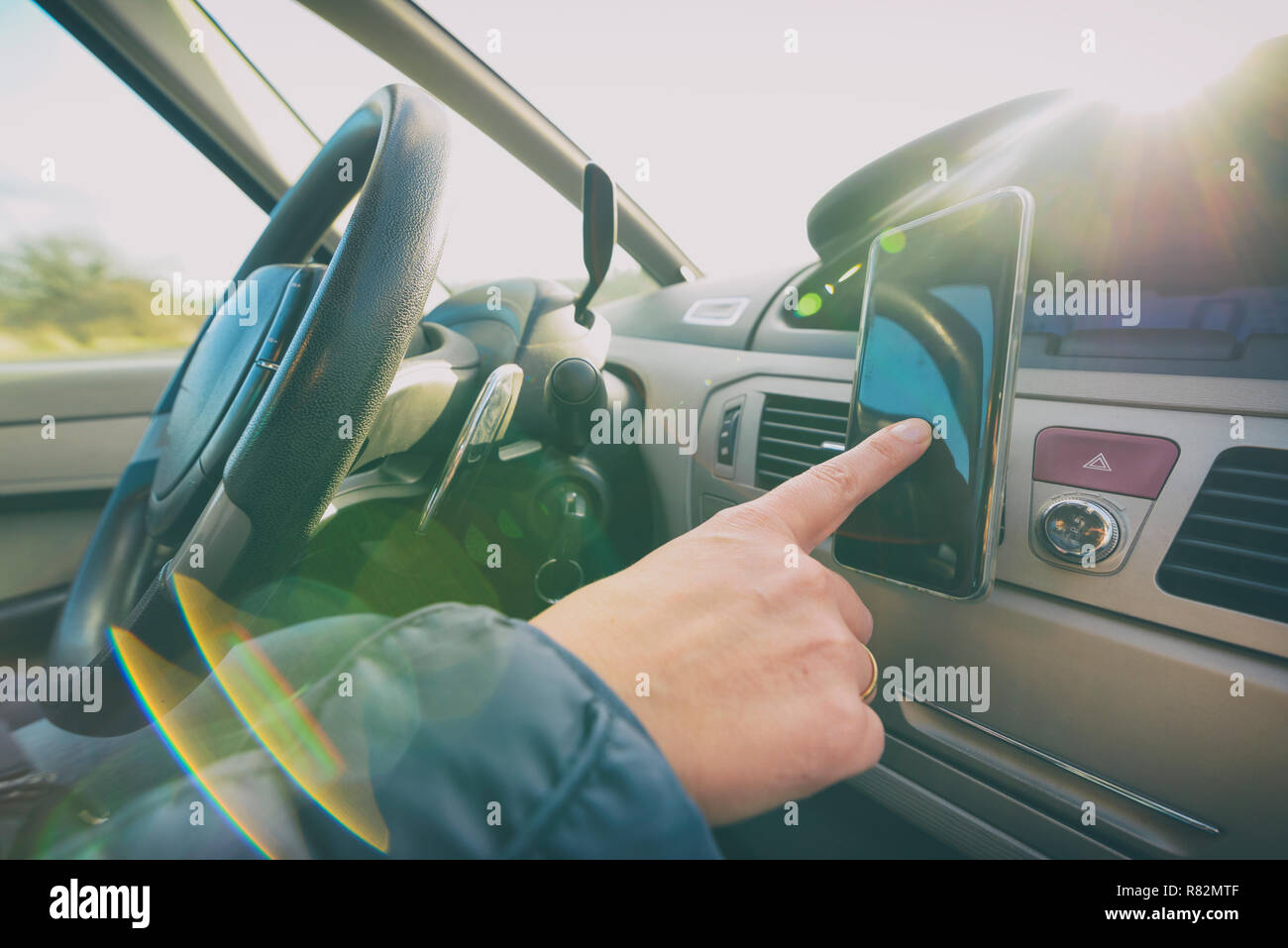 Woman using smart phone as navigation while driving the car. Risky driving behaviors concept - Stock Image