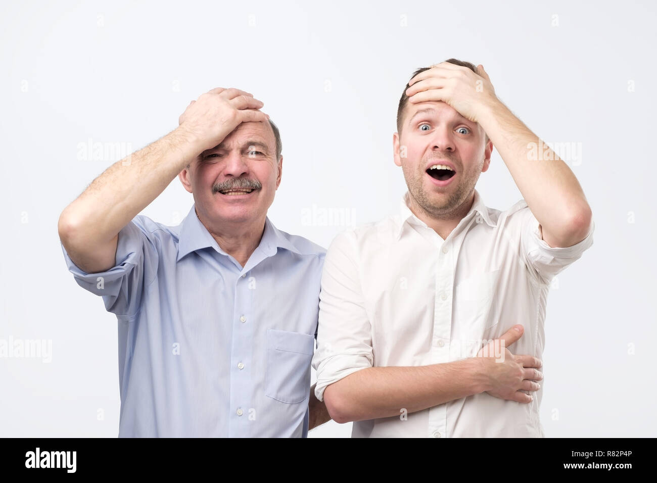 Stunned emotive two men keep jaw dropped, holding hand on head, wonder seasonal discounts and prices - Stock Image