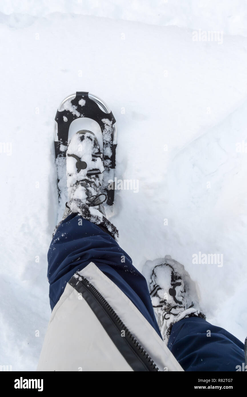 A woman in winter clothes wears snowshoes and stomps in high snow. Personal perspective. - Stock Image