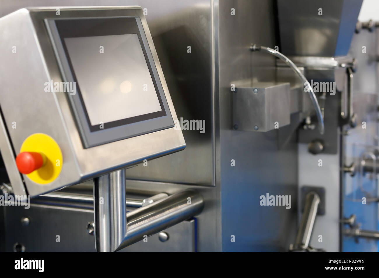 Modern stainless steel manufacturing equipment with the touchscreen control panel on the foreground. Selective focus. - Stock Image