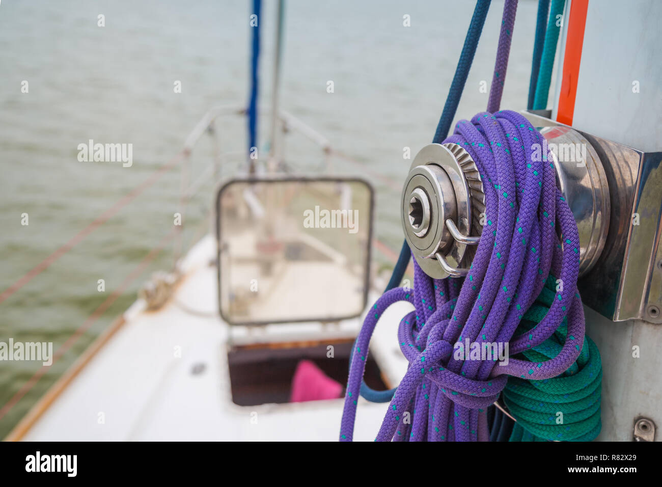 Winch mounted on the mast with ropes wound around it against the background of an open hatch in front of the yacht - Stock Image