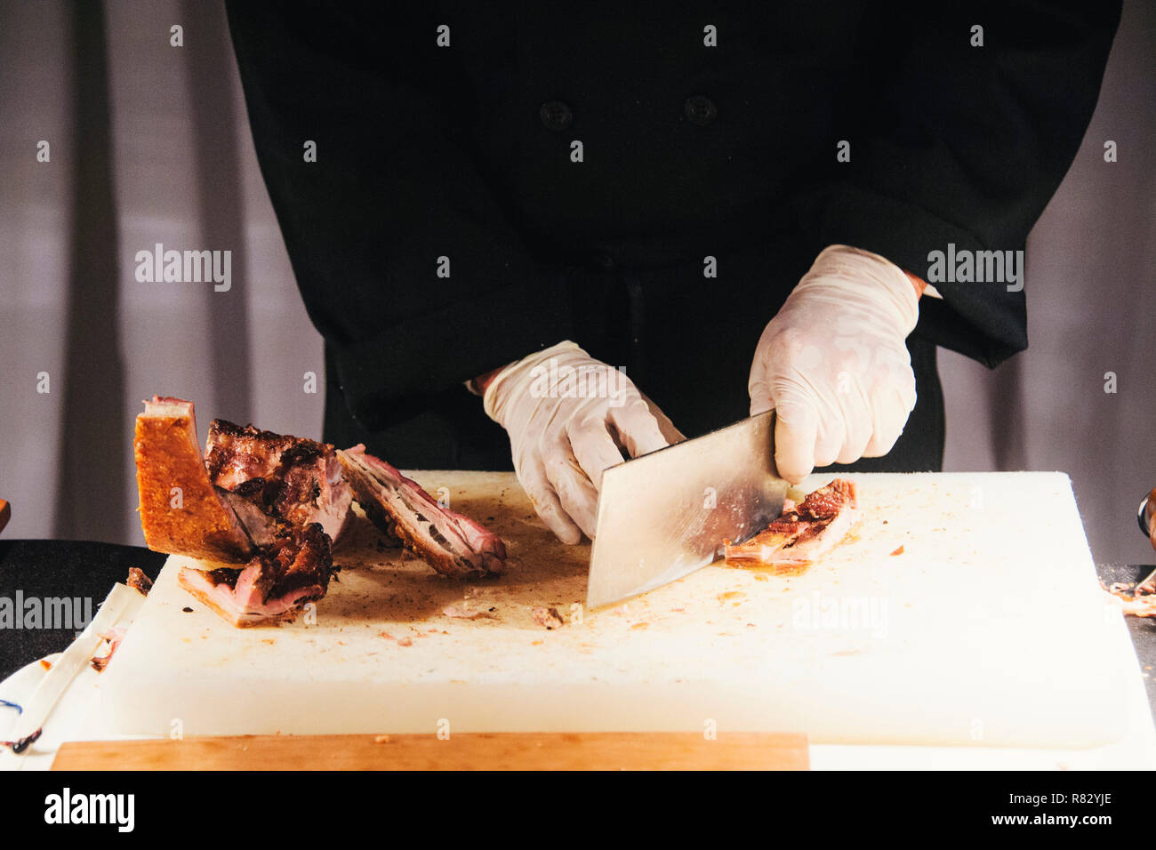 Hands of a male chops roast pork with a cleaver at a holiday party - Stock Image